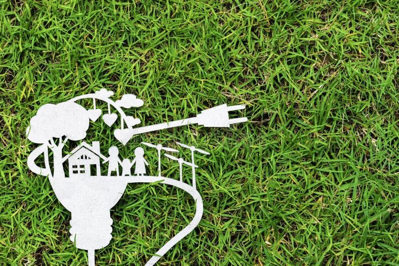 Papieru cięcie eco na zielonej trawie Opowieści o energooszczędnym obraz royalty free