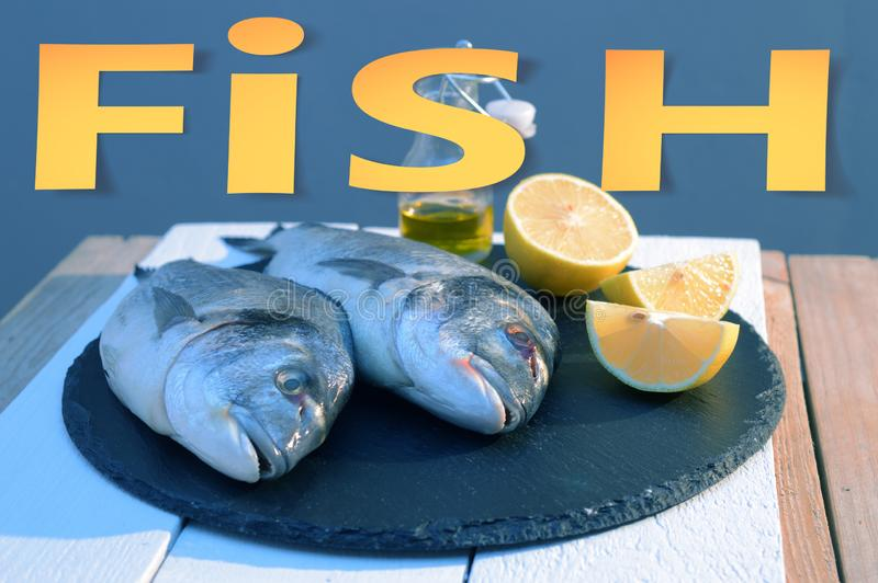Papieru cięcie za słowo rybie z miękkimi cieniami origami na dorado rybie na czarnym talerzu z cytryny i oliwy z oliwek butelki t obraz stock