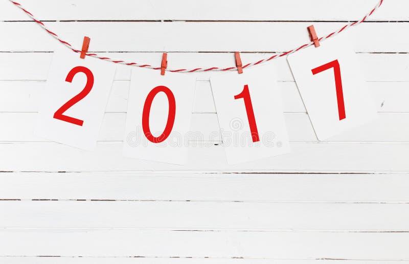 Papieru lub fotografii ramy z 2017 postaciami wiesza na czerwonej pasiastej arkanie projekta nowy rok Na drewnianym tle fotografia stock