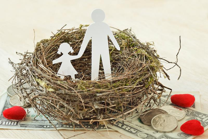 Papiervater und Tochter im Nest auf Geld und Herzen - Konzept der Alleinerziehendefamilie lizenzfreies stockbild