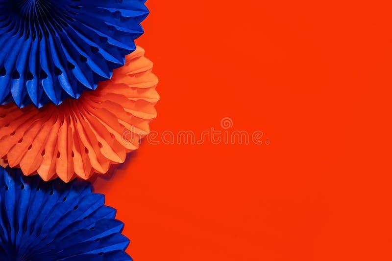 Papierventilatoren und Honigwaben auf orangefarbenem Hintergrund lizenzfreies stockfoto