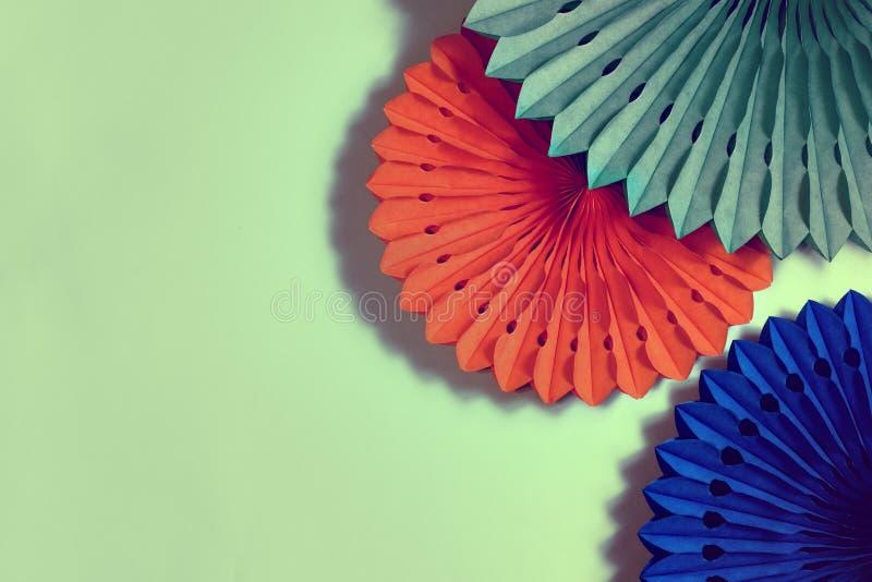 Papierventilatoren und Honigwaben auf orangefarbenem Hintergrund lizenzfreie stockfotografie