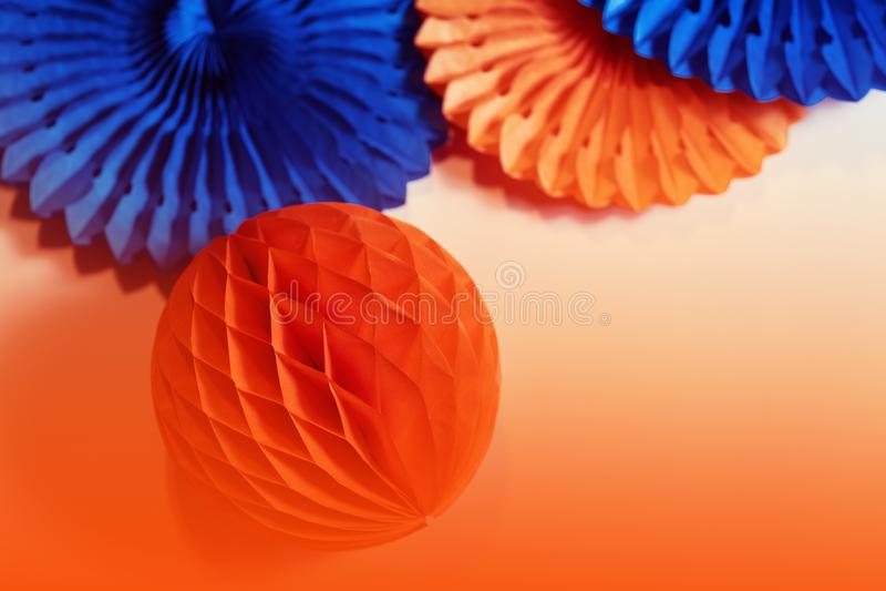 Papierventilatoren und Honigwaben auf orangefarbenem Hintergrund stockbild