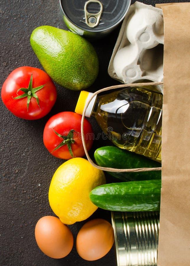 Papierzak met diverse kruidenierswaren op een donkere betonnen achtergrond Voedselleveringsconcept Voedseldonaties stock fotografie
