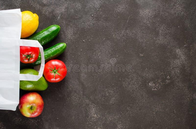 Papierzak met diverse kruidenierswaren op een donkere betonnen achtergrond Voedselleveringsconcept Voedseldonaties royalty-vrije stock foto