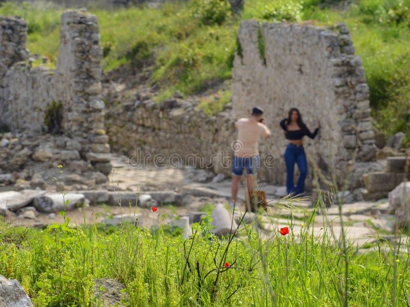 Papoilas vermelhas em um fundo borrado dos turistas que tomam imagens ao lado das ruínas antigas fotografia de stock