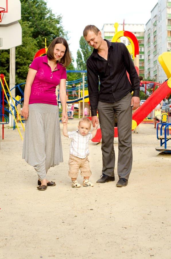 Pappa, mamma och liten son på lekplats royaltyfri bild