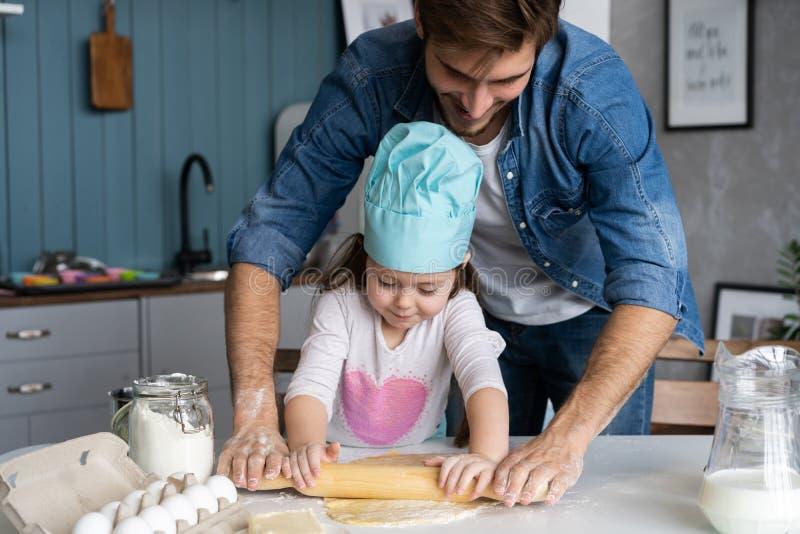 Pappa med dotterbakningkakan tillsammans i hem- kök royaltyfria foton