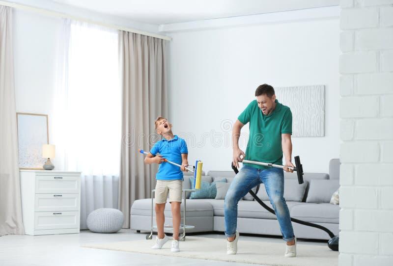 Pappa och son hade kul när de städade vardagsrummet arkivfoton