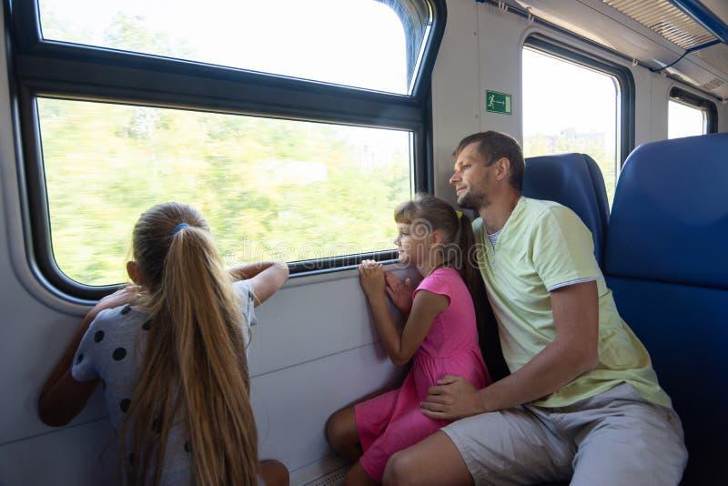 Pappa och två döttrar i en eltågsbil, titta på fönstret med entusiasm royaltyfri foto