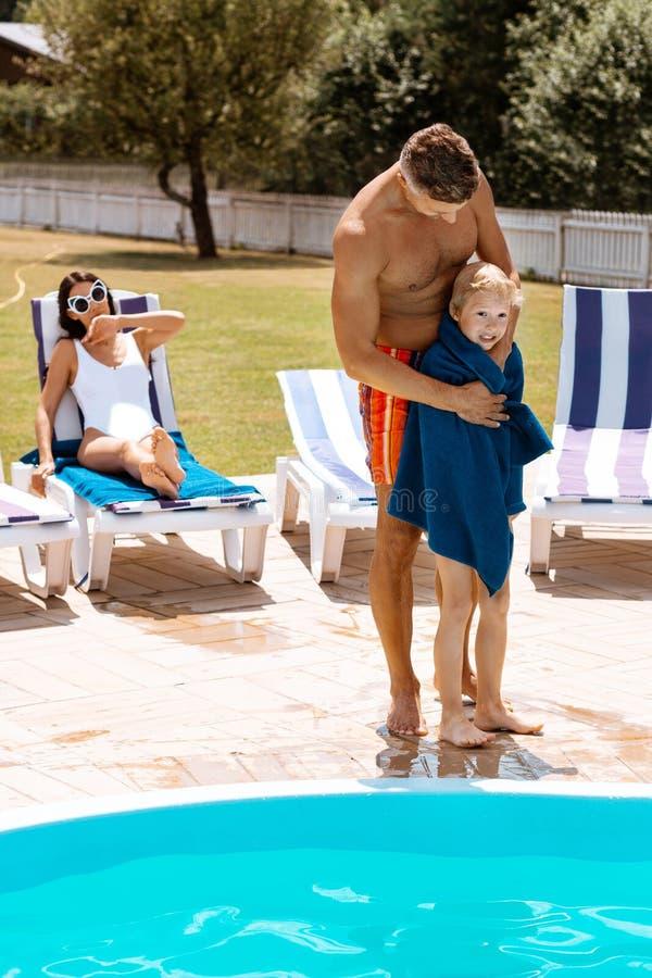 Pappa som ger hans sonhandduk, når att ha simmat i pöl arkivfoton