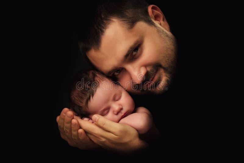 Pappan kramar hans nyfött behandla som ett barn Faders förälskelse Närbildstående på en svart bakgrund royaltyfri fotografi