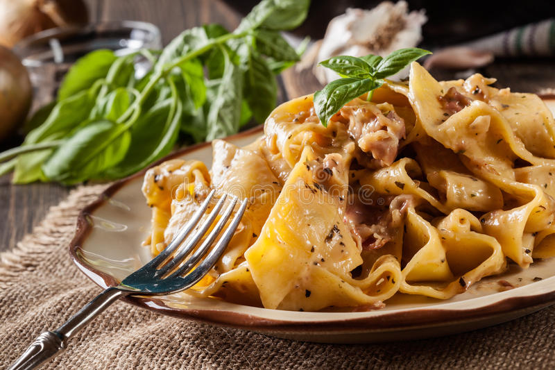 Pappardelle pasta with prosciutto and cheese sauce on a plate royalty free stock images