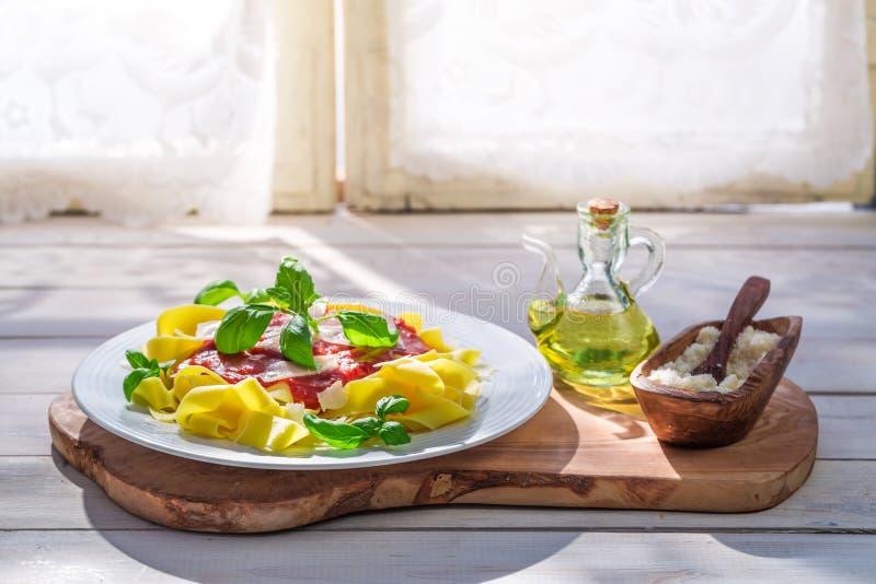 Pappardelledeegwaren met tomaat, basilicum en parmezaanse kaas in de zonnige keuken royalty-vrije stock foto