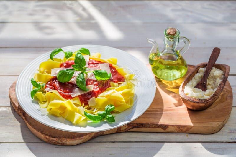 Pappardelledeegwaren met tomatensaus en basilicum in de zonnige keuken royalty-vrije stock afbeelding