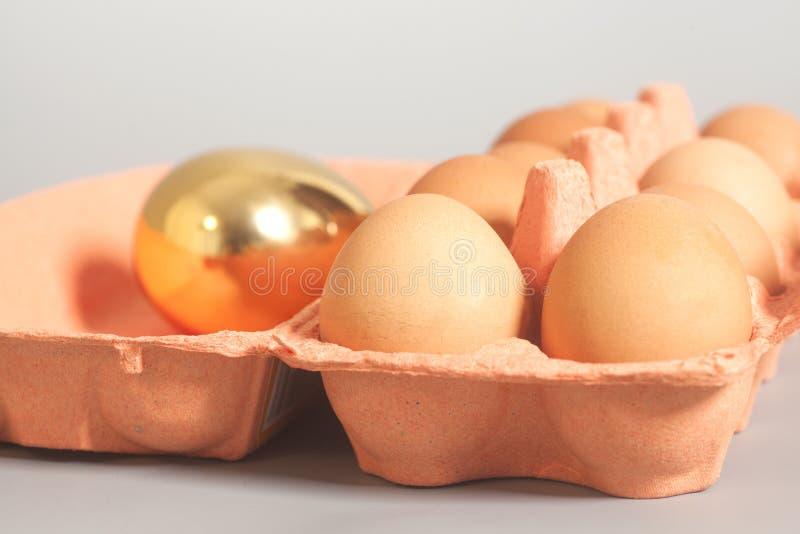 Pappeikasten mit Goldenem und Hühnereien auf grauem backgroun stockfoto