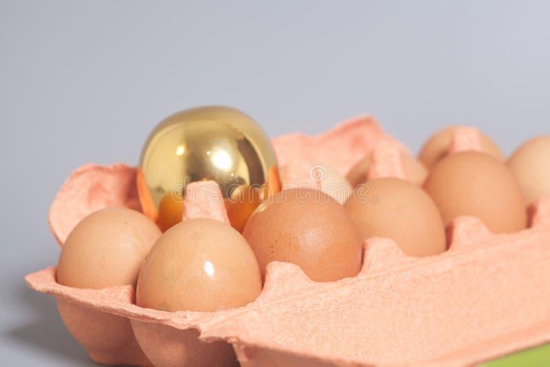 Pappeikasten mit Goldenem und Hühnereien auf grauem backgroun lizenzfreies stockfoto