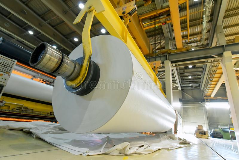 Papper för maskiner rullar för tillverkning av för ytterligare processin arkivbild