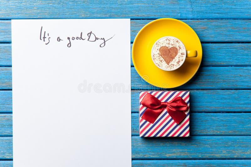 Papper, gåva, kaffe och bärbar dator som ligger på tabellen arkivfoton