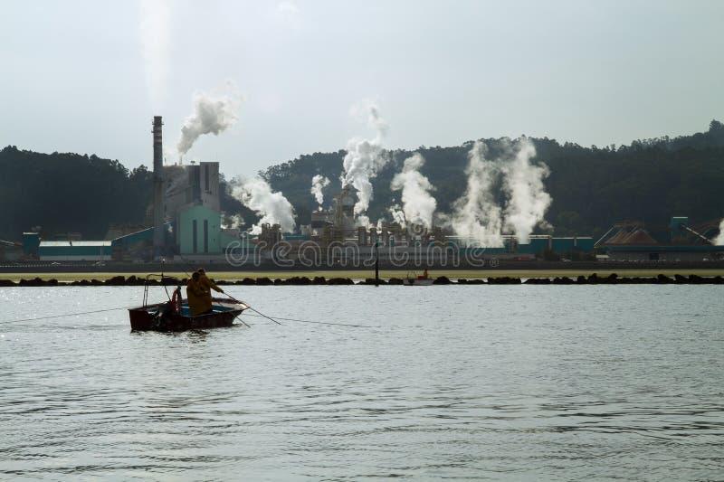 Papper maler fabriken nära en havsfjord arkivbild