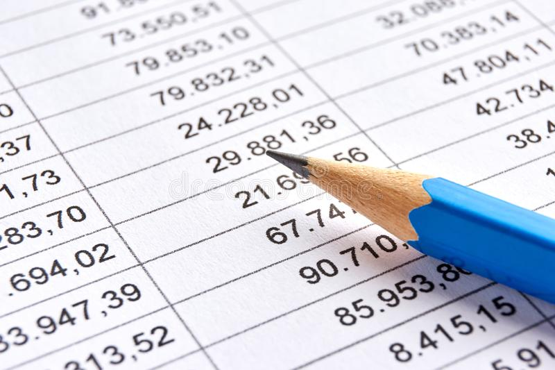 Papper med utskrivavna finansiella data och den bl?a blyertspennan arkivfoto