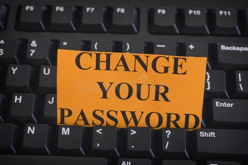 Pappers- anmärkning med uttrycksändring ditt lösenord på den svarta datoren ke royaltyfri fotografi