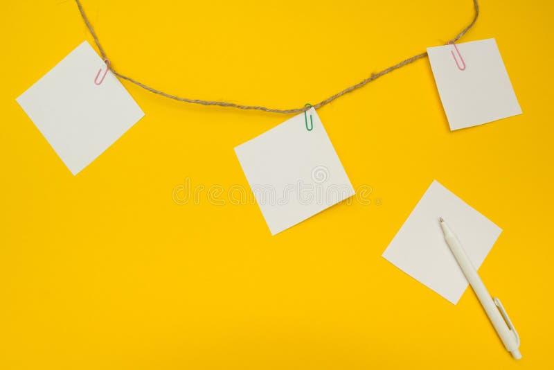 Pappers- anmärkning och penna på isolerad gul bakgrund, begrepp fotografering för bildbyråer