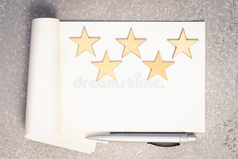 Pappers- anteckningsbok, fem trästjärnor och penna arkivfoton