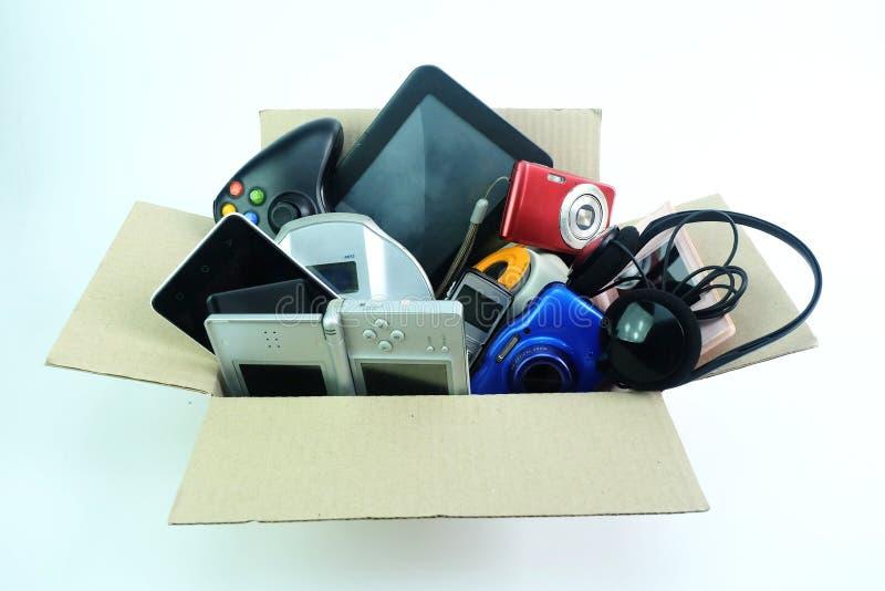 Pappers- ask med de skadade eller gamla använda elektronikgrejerna för dagligt bruk på vit bakgrund arkivbild