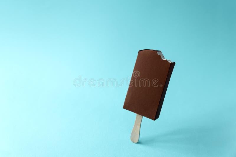 Pappers- biten vaniljglassisglass som täckas med choklad på blå bakgrund kopiera avstånd Idérik eller konstmatbegrepp fotografering för bildbyråer