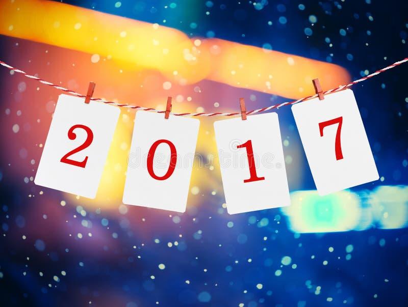 Pappers- eller fotoramar med 2017 diagram som hänger på det röda randiga repet Snöfallbakgrund, design för nytt år arkivbilder