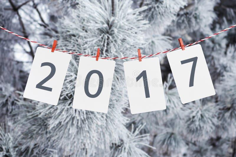 Pappers- eller fotoramar med 2017 som hänger på det röda randiga repet Fotoet av ett snöig sörjer på bakgrund nytt år för design royaltyfria foton