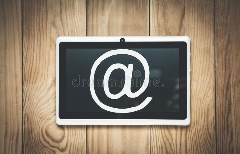 Pappers- emailsymbol med minnestavlan på den wood bakgrunden royaltyfria bilder