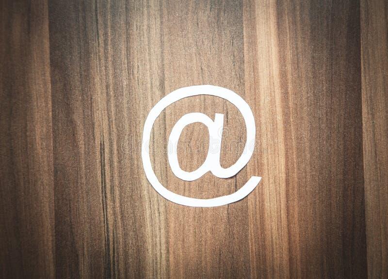 Pappers- emailsymbol på den wood bakgrunden royaltyfri fotografi
