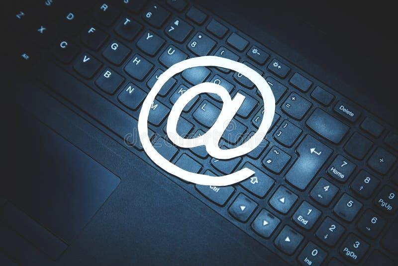 Pappers- emailsymbol på det svarta bärbar datortangentbordet arkivfoton