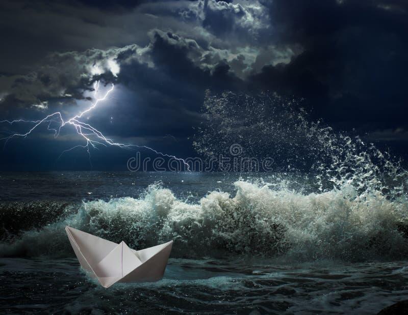 Pappers- fartyg i havstorm med lgihting och vågor royaltyfria bilder