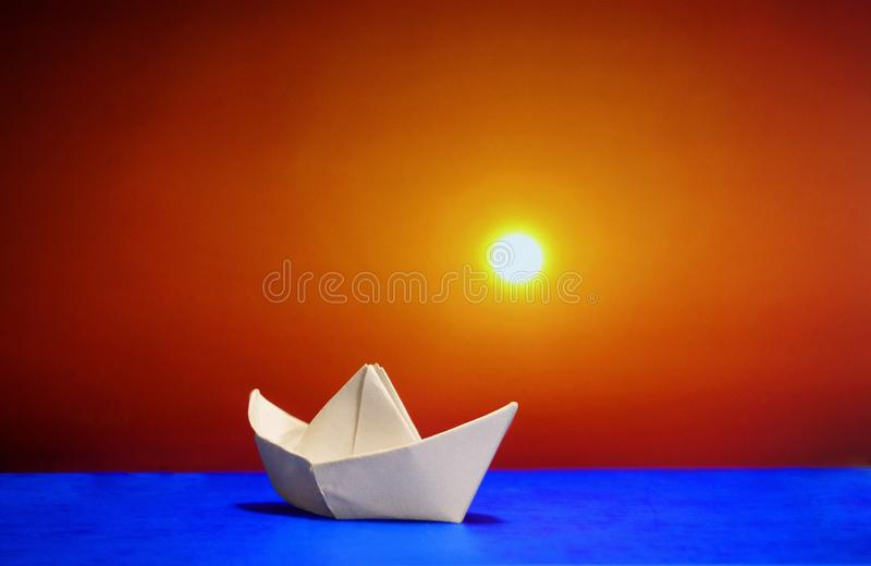 Pappers- fartyg på bakgrunden av solnedgången arkivbilder