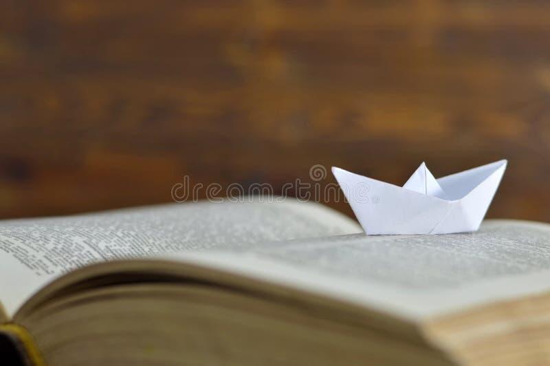 Pappers- fartyg på boken royaltyfria foton