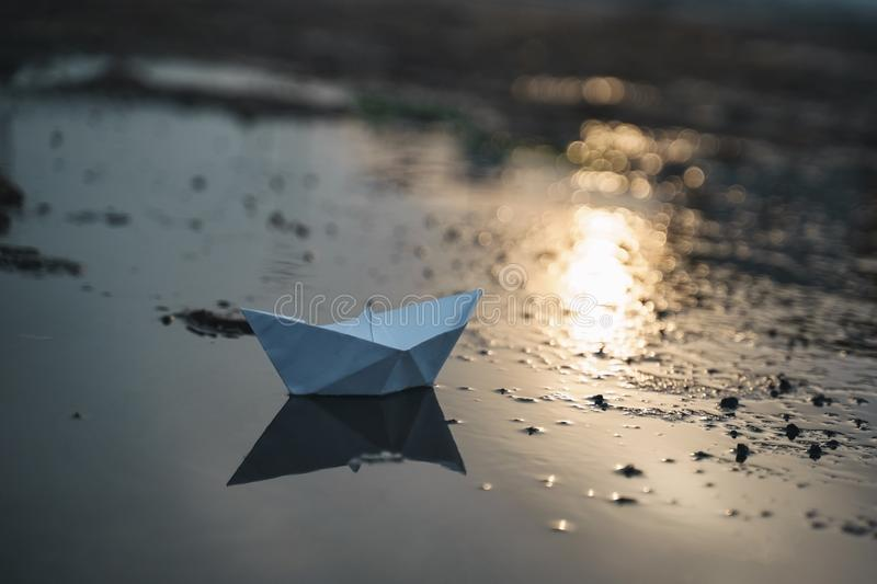 Pappers- fartyg på stranden på solnedgångtid arkivbilder