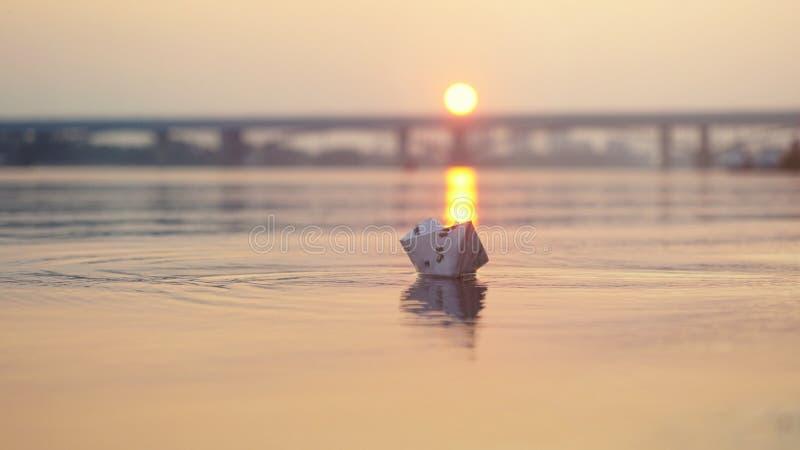 Pappers- fartyg på vattnet under härlig solnedgång med reflexionssolen i havet Överbrygga bakgrunden arkivfoto