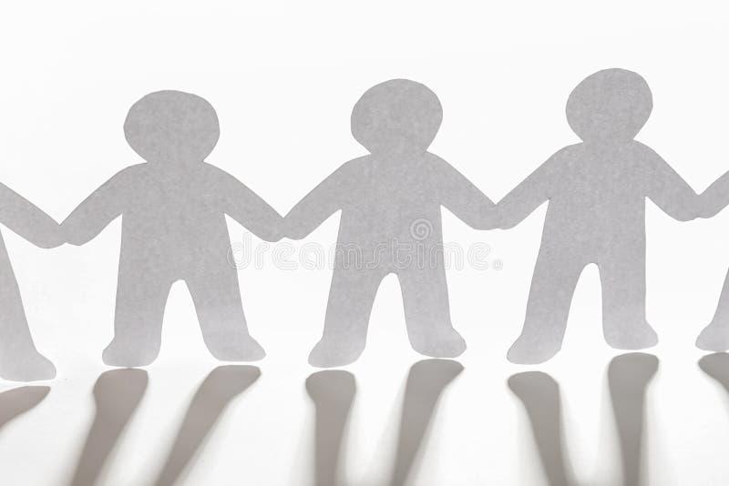 Pappers- folk som rymmer händer på ljus bakgrund royaltyfri foto