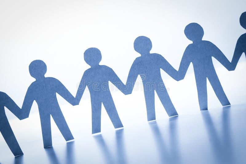 Pappers- folk som tillsammans står handen - in - hand Lag samhälle, affärsidé arkivfoto