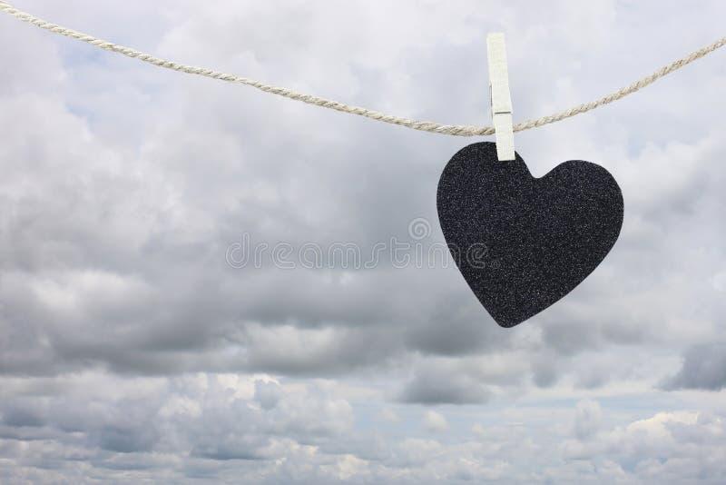 Pappers- hänga för svart hjärta på ett brunt hamparep på lodisar för regnmoln royaltyfri bild