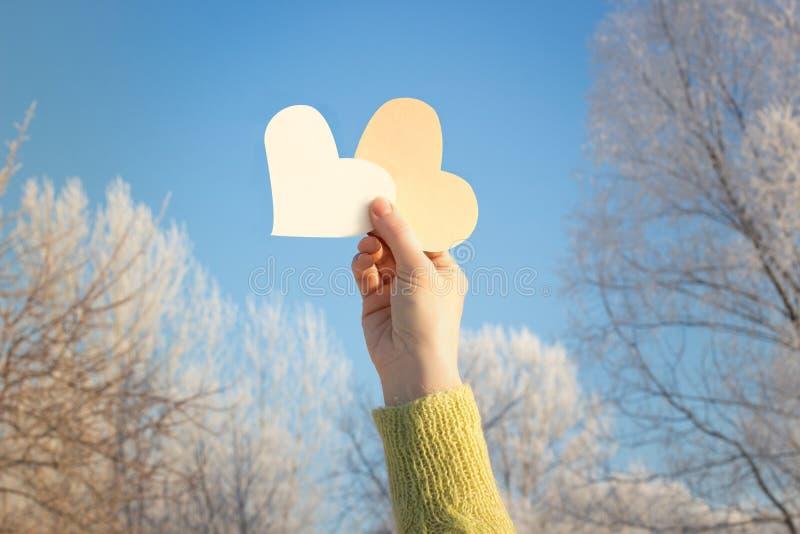 Pappers- hjärta i händer arkivbild