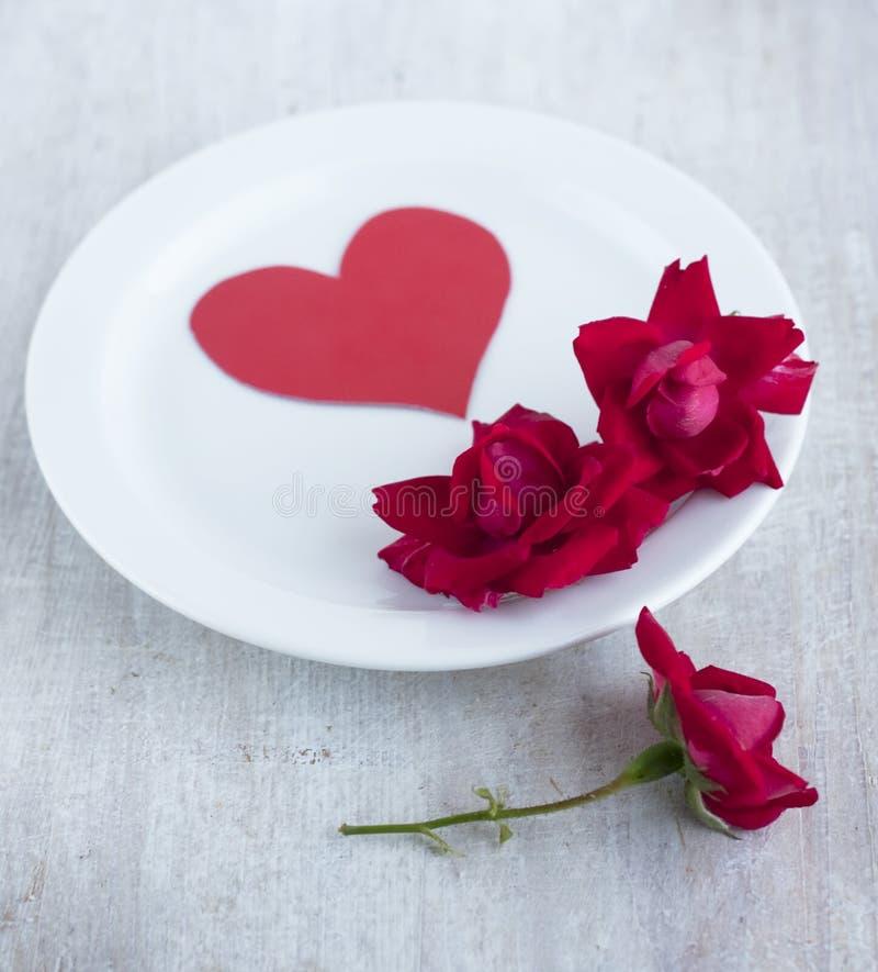 Pappers- hjärta och scharlakansröda rosor på vitrundaplattan arkivbild