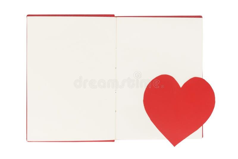 Pappers- hjärtabokmärke på den öppna boken för mellanrum som isoleras på vit royaltyfri foto