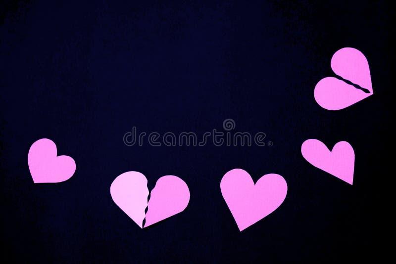 Pappers- hjärtor för rosa färger på ett svart bakgrunds- och kopieringsutrymme royaltyfria foton
