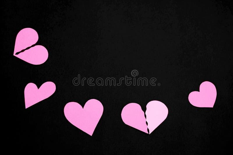 Pappers- hjärtor för rosa färger på ett svart bakgrunds- och kopieringsutrymme arkivbilder