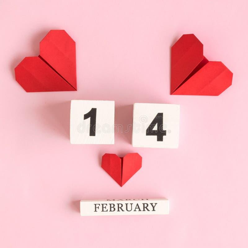 Pappers- hjärtor och träkalender med datum 14 av februari abstrakt begrepp på ros royaltyfria foton
