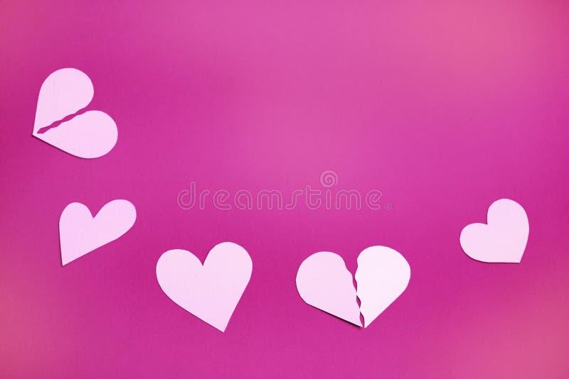 Pappers- hjärtor på ett rosa bakgrunds- och kopieringsutrymme arkivfoto